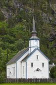 Traditional norwegian white stave church. Valldal Sylte stavkyrkje . Travel Norway. Vertical poster