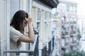 young sad beautiful woman suffering depression looking worried and wasted on home balcony with an urban view in lonely depressed and crying desperate female concept poster