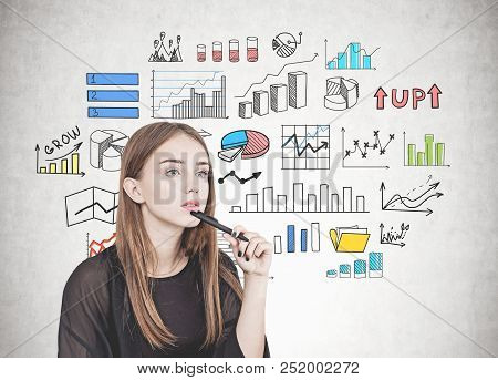 Pensive Young Woman With Long Fair Hair Holding A Pen Near Her Chin. Types Of Graphs Drawn On A Conc