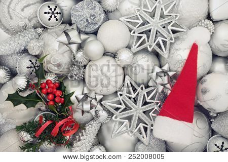 Christmas background with white and silver baubles, santa hat and holly and fir decorations. Traditional christmas greeting card for the holiday season. Top view.