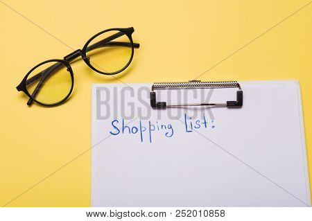 List Of Paper With Words Shopping List On Yellow Background. Copy Space.