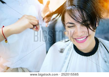 Beauty, hairstyle, treatment, hair care concept, young woman and hairdresser cutting hair at hairdressing salon. Hairdresser cuts happy girl's hair. Hairstylist serving client at barber shop