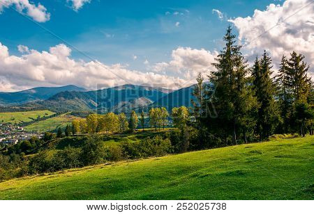 Beautiful View In To The Rural Valley. Gorgeous Countryside With Forest On Grassy Hill And Distant M