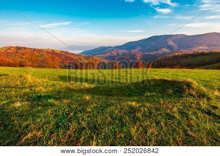 Grassy Meadow On Hill Side At Sunrise In Autumn. Beautiful Mountainous Landscape With Distant Valley