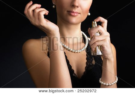 Elegant woman with perfume on black. Focus on hands and perfume.