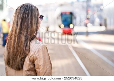 Back View Of Woman Waiting For Tram In Stop. Passenger Looking At Arriving City Train At Station. Co