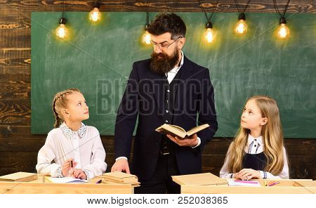 Learning At Home. Sisters Learning Literature At Home. Learning At Home With Serious Teacher. Learni
