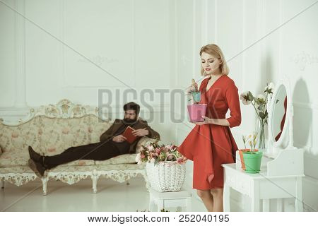 Plant Concept. Pretty Woman Grow Young Plant In Pot While Man Relax On Sofa. Plant Seedling And Grow