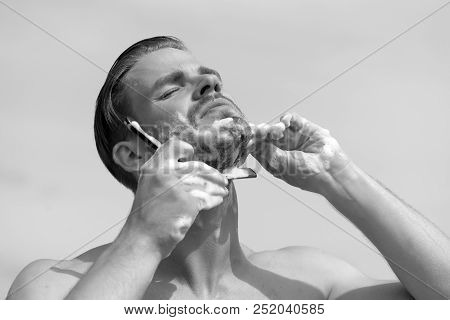Man With Bristle On Clear Sky Background. Macho Shaving Chin With Razor On Clear Sky Background