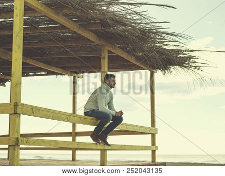 Young man on the beach. The guy enjoying the warm autumn day. Portrait of man near the water colored filter