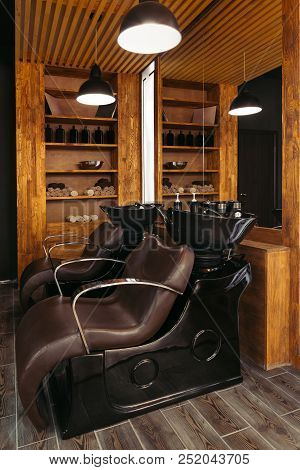 Empty Leather Chairs And Sinks In Modern Hair Salon