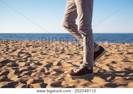 Close Up Image Of Man Legs Walking Alone Sandy Beach With Blue Ocean And White Sand, Wearing White T