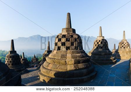 Borobudur Temple And Bell-enshrined Buddhas Looking Over The Jungle And Mountains Of Java, Indonesia