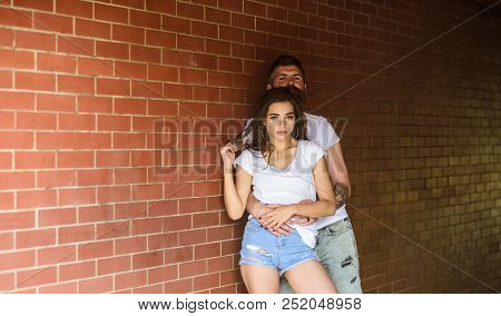 Couple Find Place To Be Alone. Couple In Love Hugs Brick Wall Background. He Will Never Let Her Go.