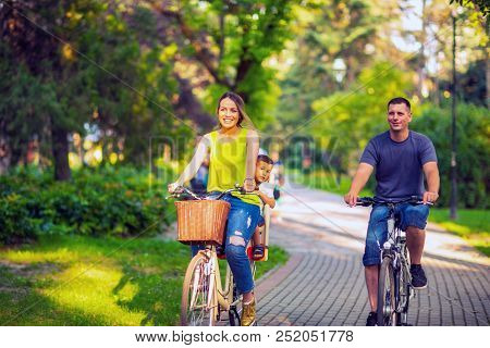 Happy Family. Smiling Active Father And Mother With Kid On Bicycles Having Fun In Park. Family Sport