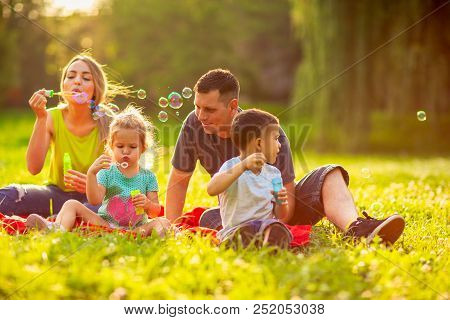 Happy Family In The Park- Young Family With Children Blow Soap Bubbles Outdoor