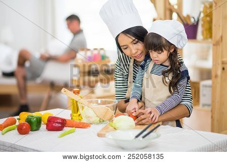 Beautiful Mother Teaches Her Daughter Hoe To Prepare Breakfast In The Kitchen; Family Happy At Home.