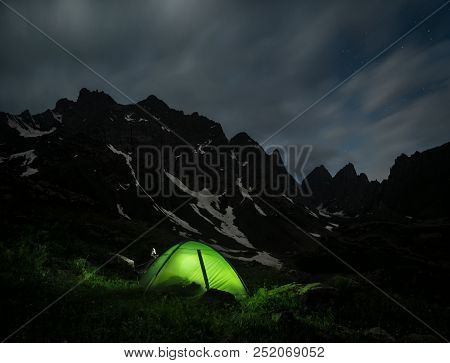 Night Landscape Of A Camping Tent And A Mountain Range At The Background. Chaukhi Mountain Range At