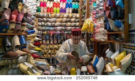 Fez, Morocco - April 2018: Unkown Man Selling Slippers And Shoes In Traditional Store In Fes, Morocc