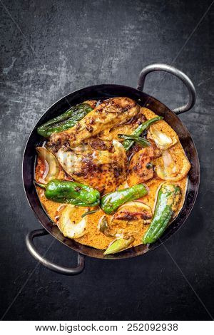 Traditional Thai kaeng massaman coconut chicken curry with jalapeno, poblano chili and sweet potatoes as top view in a traditional bowl
