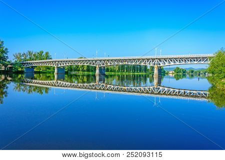 Steel Bridge Over The Labe River In Litomerice. The Reflection Of The Bridge On The River. Sunrise O