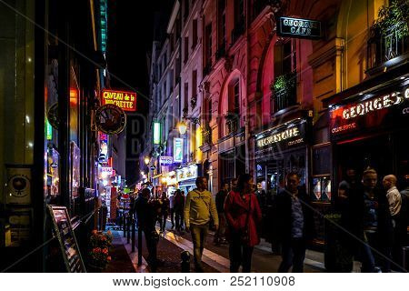 Paris, France - September 23 2017: Bouncers Watch Tourists And Locals Pass By Outside A Bar Late At