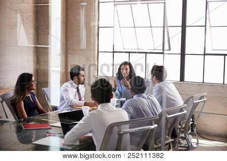 Businesswoman and colleagues sitting at a boardroom meeting