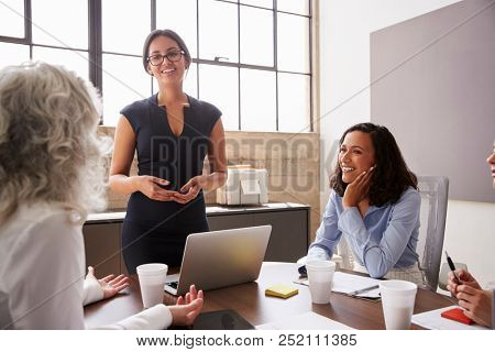 Female manager in glasses addressing businesswomen in meeting