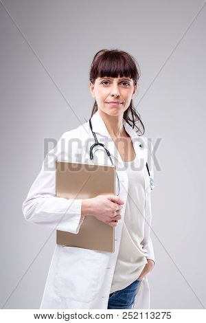 Busy Female Doctor Pausing To Look At The Camera