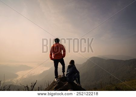 Young Couple Traveler Standing And Looking At Beautiful Landscape On Top Of Mountain
