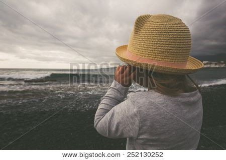 Cute Little Girl Stays On Coast Of The Sea In Hat During Stormy Clouds. Vintage Style Photography.