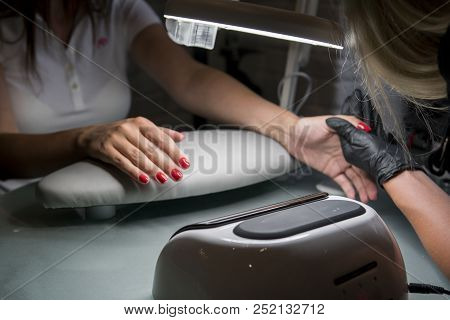 Woman having a nail manicure in a beauty salon with a closeup view of a beautician applying varnish with an applicator. Master painted nails with nail polish. Details shot of hands applying red nail. poster