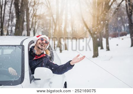 Portrait Of Car Driver With Santa Hat Through Car Window Enjoying The Snowy Day. On The Road Winter