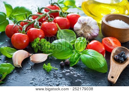Ripe tomatoes with fresh basil, garlic and other herbs with water drops on slate plate. Mediterranean food healthy diet. Fresh vegetables spices and Italian herbs