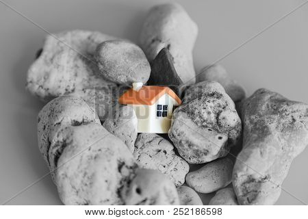 Miniature Toy House Fallen Into A Crack In The Earth. Earthquake Symbol. The Concept Of The Threat A