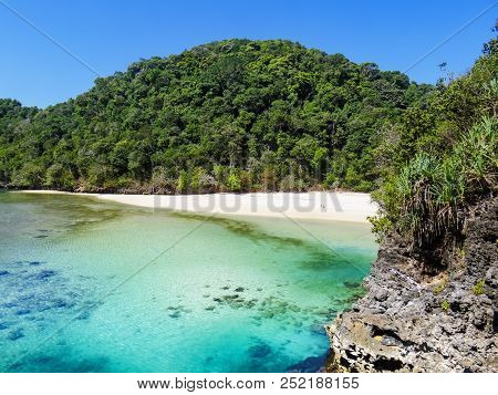 People Relax On Desert White Sand Beach After Trekking In Tropical Jungle To Segara Anakan Lagoon Wi