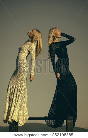 Opposites And Contrasts Concept. Women Wearing Black And White Dresses. Two Girls With Long Blond Ha