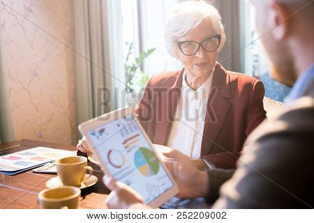 Senior Businesswoman Wearing Eyeglasses Communicating With Her Partner With Touchpad At The Table At