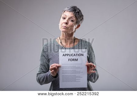 Expectant Woman Holding Up An Application Form