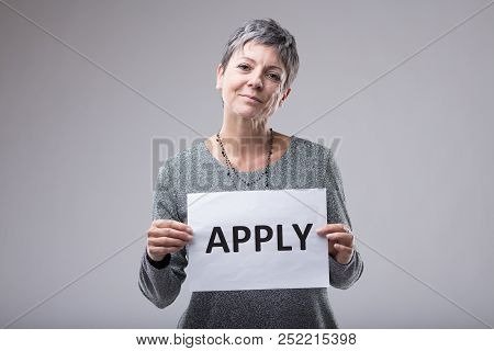 Smiling Confident Woman Holding A Sign - Apply