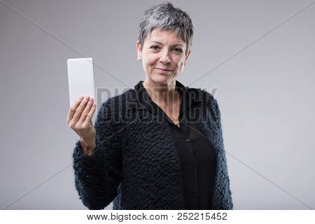 Older Attractive Woman Holding Up A Mobile Phone