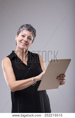 Attractive Middle-aged Businesswoman Using Tablet