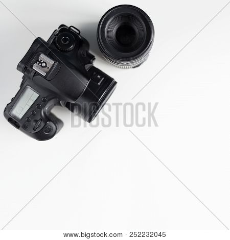 Modern Photo Camera And Lens Over White Table Background