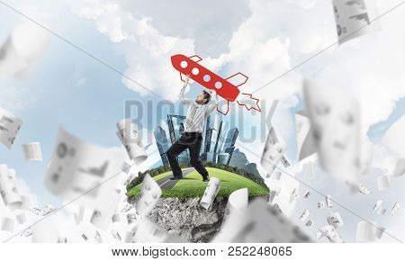 Horizontal shot of successful and young businessman standing among flying papers on the flying island and throwing huge rocket in the air with cloudy skyscape view on background. poster