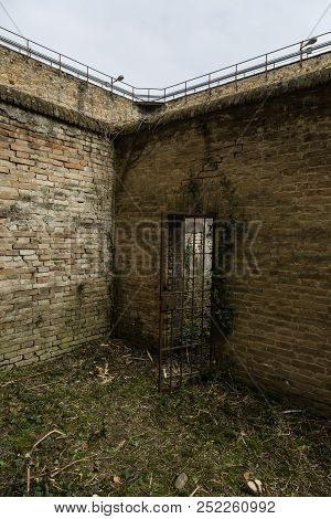 Parma, Italy - March 2018: Unkempt Courtyard Of An Old Prison Full Of Weeds And Cells.