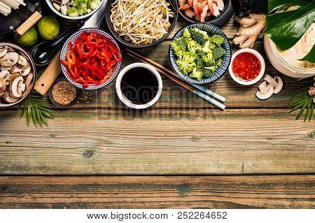 Asian Cuisine Ingredients On Wooden Background, Top View. Vegetables, Spices, Shrimp, Noodles, Sauce