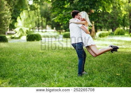 The Lovely Beautiful Couple In Love Sitting On Green Grass. Romantic Love Story In The Park. Young G
