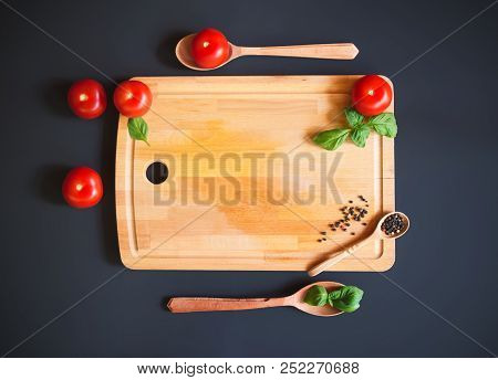 Tomatoes, Pepper And Green Basil Leaves On Wooden Cutting Board On Dark Background