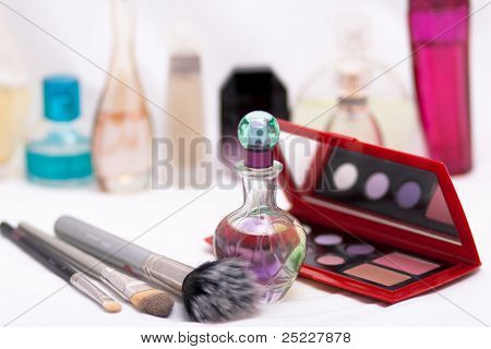 Perfume brushes and compact isolated with bottles in the background