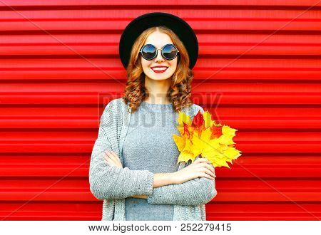 Stylish Autumn Woman Holds Yellow Maple Leaves On A Red Background